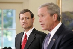 John Roberts appears in the background, as President Bush announces his nomination of Roberts for the position of Chief Justice.
