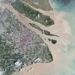 This natural-color satellite image shows the urban area of Shanghai in 2016, along with its major islands of (from northwest to southeast) Chongming, Changxing, Hengsha, and the Jiuduansha shoals off Pudong. Yangtze's natural sediment discharging can be seen.