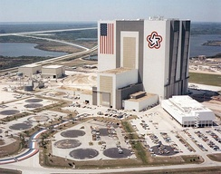 The NASA Vehicle Assembly Building in 1977. The VAB has the largest U.S. flag ever used on a building, and with the Bicentennial Star opposite the flag.