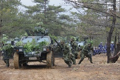 JGSDF soldiers rush out of their LAV to counter an ambush.