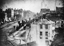 View of the Boulevard du Temple, a daguerreotype made by Louis Daguerre in 1838, is generally accepted as the earliest photograph to include people. It is a view of a busy street, but because the exposure lasted for several minutes the moving traffic left no trace. Only the two men near the bottom left corner, one of them apparently having his boots polished by the other, remained in one place long enough to be visible.