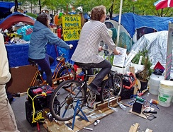 Protesters at Occupy Wall Street using bicycles connected to a motor and one-way diode to charge batteries for their electronics[20]