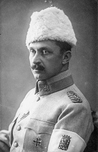 A studio-style picture of General Mannerheim, commander-in-chief of the White Army. He is looking away with his left shoulder turned towards the camera. On his left arm, an armband shows the coat of arms of Finland.