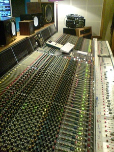 Neve VR60, a multitrack mixing console. Above the console are a range of studio monitor speakers.