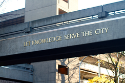 The university's motto on a campus skybridge over SW Broadway St.