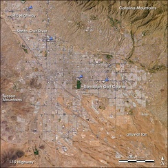 Tucson, as seen from space. The city's four major malls are indicated by blue arrows.