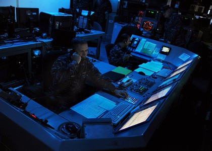 U.S. Navy officers aboard the aircraft carrier USS Abraham Lincoln monitor defense systems during early 2010s maritime security operations exercises