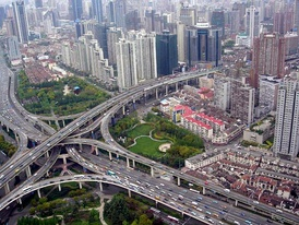 A multi-level stack interchange, buildings, houses, and park in Shanghai, China.