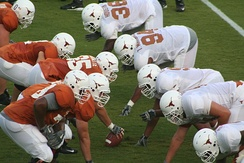 The offensive line (on left, in orange jerseys) consists of a center (with ball in hand ready to snap) with two guards on either side, and two tackles.