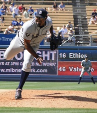 A man with a gray uniform and navy blue hat throws a pitch.