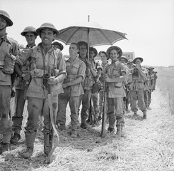 Men of the 6th Battalion, Royal Inniskilling Fusiliers, British 78th Division, await orders to move into Centuripe, Sicily, 2 August 1943.
