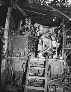 New Guinea in 1943. Mobile machine shop truck of the US Army with machinists working on automotive parts