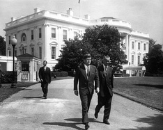 President Kennedy and Vice President Johnson take a leisurely stroll on the White House grounds