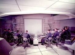 Subsector Command Post of SAGE Combat Center at Syracuse Air Force Station with consoles and large display, which was projected from above. Archive photo taken during equipment installation.