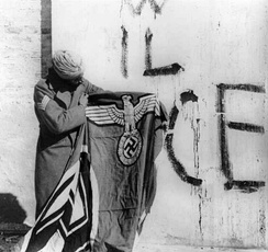 Indian soldier with captured swastika flag after surrender of German forces in Italy, May 1945