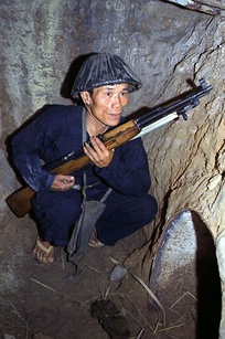Viet Cong soldier crouches in a bunker with an SKS rifle