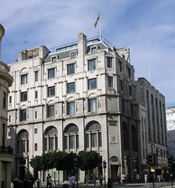 An Edwardian building with six floors stands on a moderate day, a flag flying atop it.