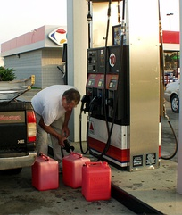 A man using a fuel dispenser by pumping gasoline into plastic fuel containers