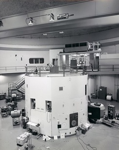 The black and white photograph is of a large room that contains a lot of electronic equipment. The lower half of the image contains a cylindrical white container that is a nuclear reactor. There is a walkway at the top of the reactor, which leads back to a control room where two men are sitting.