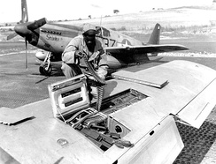 A USAAF armourer of the 100th Fighter Squadron, 332nd Fighter Group, 15th U.S. Air Force checks ammunition belts of the 12.7 mm machine guns in the wings of a North American P-51B Mustang in Italy, ca. September 1944.