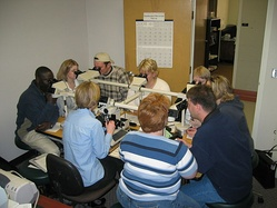 An anatomical pathology instructor uses a microscope with multiple eyepieces to instruct students in diagnostic microscopy.