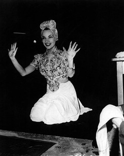 A smiling Miranda, in costume, holds up her hands after leaving her prints outside Grauman's Chinese Theatre.