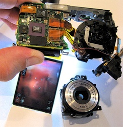Digital camera, partly disassembled. The lens assembly (bottom right) is partially removed, but the sensor (top right) still captures an image, as seen on the LCD screen (bottom left).