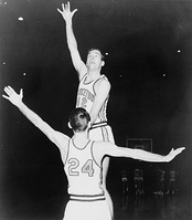"A basketball player, wearing a jersey with a word ""PRINCETON"" and the number ""42"", is jumping in front of another basketball player who is wearing a jersey with the number ""24""."