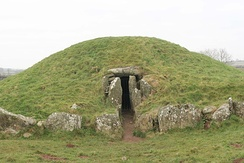 A low grassy mound with an entrance at its centre framed by cyclopean stones