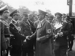 Schirach (extreme left) watches as Hitler greets his Chancellery chief Philipp Bouhler in Munich 1938.