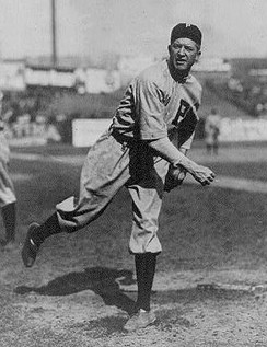 Black and white image of Grover Cleveland Alexander following through after throwing in his Phillies uniform