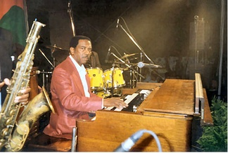 Jazz organist Jimmy Smith at a show in Italy in 1994; the sax and drumkit of the other trio members can be seen in this picture.
