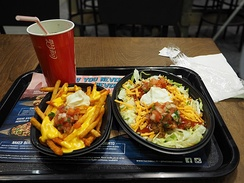 A Naked Burrito Bowl with seasoned French fries and a soft drink at a Taco Bell in Finland