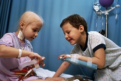 Two girls with acute lymphoblastic leukemia receiving chemotherapy. The girl at left has a central venous catheter inserted in her neck. The girl at right has a peripheral venous catheter. The arm board stabilizes the arm during needle insertion. Anti-cancer IV drip is seen at top right.