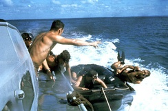 Underwater Demolition Team members using the casting technique from a speeding boat