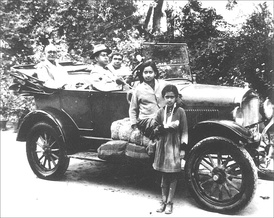 Three people sitting in an old-fashioned open car with two young girls standing in front