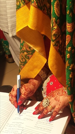 A Pakistani bride signing a marriage certificate