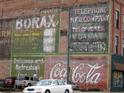 Coca-Cola ghost sign in Fort Dodge, Iowa. Older Coca-Cola ghosts behind Borax and telephone ads. April 2008.