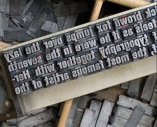 Metal type sorts arranged on a composing stick