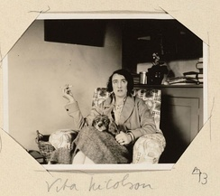 Photo of Vita Sackville-West in armchair at Virginia's home at Monk's House, smoking and with dog on her lap