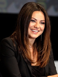 Mila Kunis smiles in a black dress