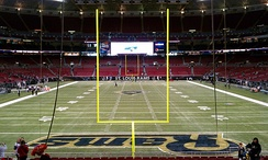 Photograph of a football field taken from the end zone showing goal posts in the foreground