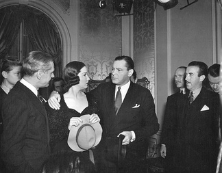 Surrounded by reporters, Gwen Taylor (Gail Patrick) and Richard Todd (Herbert Marshall) answer a barrage of questions following the press conference in Mad About Music