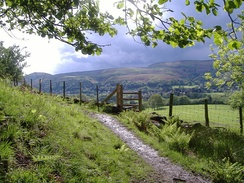 A stile and footpath with view of the Long Mynd; tourism based on the surrounding natural landscape has been important for the town's economy since the late 19th century