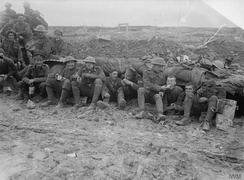 Canadian troops, possibly of the 25th Battalion (Nova Scotia Rifles), eating rations whilst seated on muddy ground outside a shelter near Pozieres, France, during the final stages of the Battle of the Somme, October 1916.