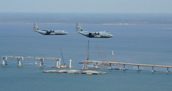 "The WC-130J (right) and C-130J-30 (left) fly over the Bay St. Louis Bridge on 20 May 2007. The 815th Airllift Squadron ""Flying Jennies"" and the 53rd Weather Reconnaissance Squadron ""Hurricane Hunters"" are part of the Air Force Reserve's 403rd Wing located at Keesler Air Force Base, Miss. The bridge was damaged by Hurricane Katrina and will re-open 17 May 2007."