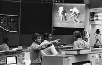 A control room; visible on a large screen are two astronauts walking on the Moon