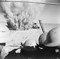A mine explodes close to a British artillery tractor as it advances through enemy minefields and wire to the new front line