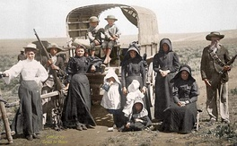 Boer family traveling by covered wagon circa 1900