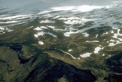 Aerial view of the Point Kadin vents, a series of post-glacial explosion pits and small cinder cones that occur along a fracture zone northwest of the summit of Makushin Volcano.